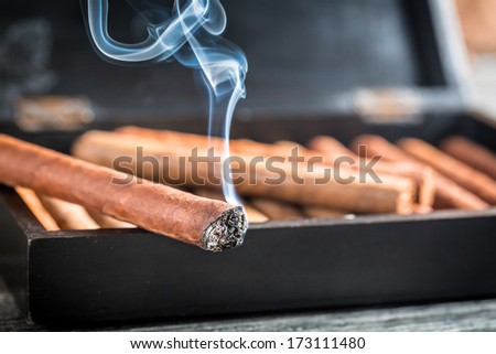 Closeup of burning cigar on wooden humidor - stock photo