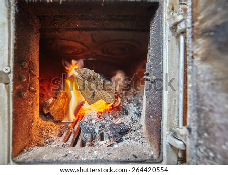 Closeup of burning firewood inside a heater with stove - stock photo