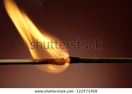 Closeup of burning match against black background - stock photo