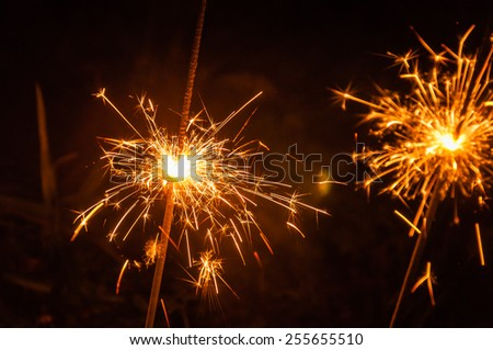 Closeup of burning sparklers with splashing sparks in the dark. - stock photo
