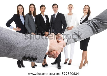 Closeup of business handshake, team of business people on background, isolated on white