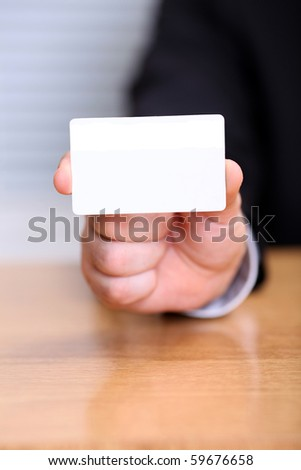 Closeup of business man holding a blank business card - stock photo