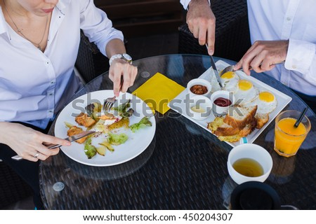 Closeup of business people hands, male and female having breakfast at outdoors cafe. Meals with salad, omelette, bacon.