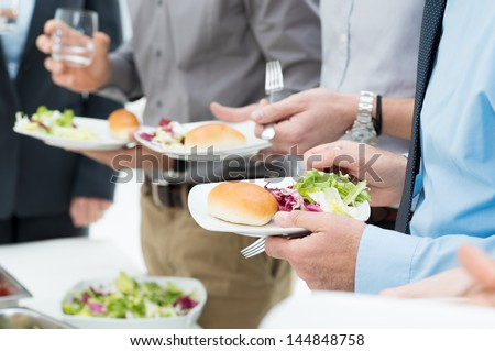 Closeup Of Business People's Hands Having Lunch Together - stock photo