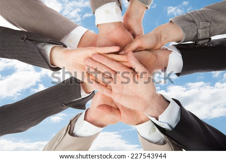 Closeup of business people's hands on top of each other symbolizing unity against sky