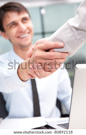 Closeup of business people shaking hands over a deal at office - Indoors