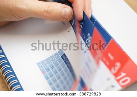 closeup of  business person hands checking calendar - stock photo