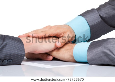 Closeup of business team putting their hands on top of each other on office desk, in elegant modern suit, isolated over white background. - stock photo