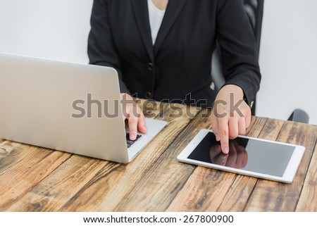 Closeup of business woman hand typing on laptop keyboard and tablet - stock photo