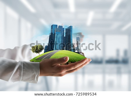 Closeup of business woman in shirt keeping green island with skycraper city in her hands with office view on background. Mixed media.