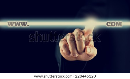 Closeup of businessman activating a www.com button on virtual screen, toned retro effect. - stock photo