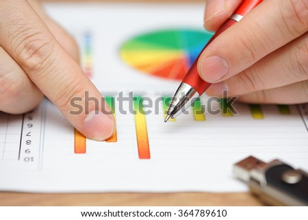 closeup of businessman analyzing business data on graphs and diagrams - stock photo