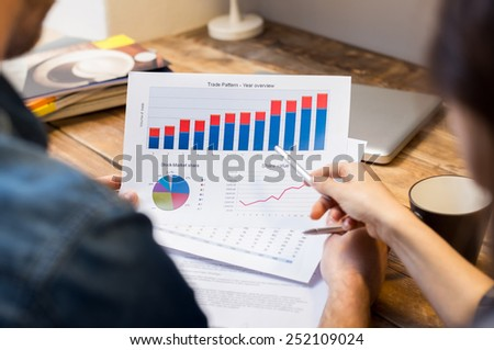 Closeup of businessman and woman discussing on stockmarket document in office  - stock photo