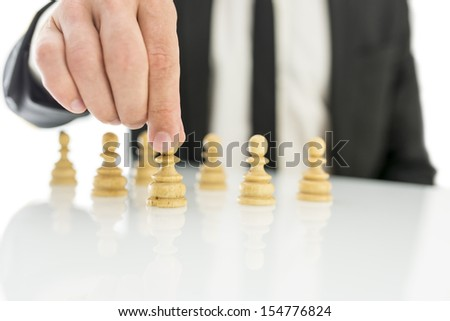 Closeup of businessman arranging chess figures pawns. Concept of human resources. - stock photo