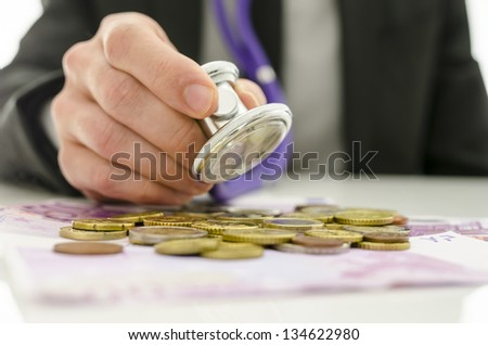 Closeup of businessman checking Euro coins and banknotes with stethoscope. Concept of financial crisis solution. - stock photo