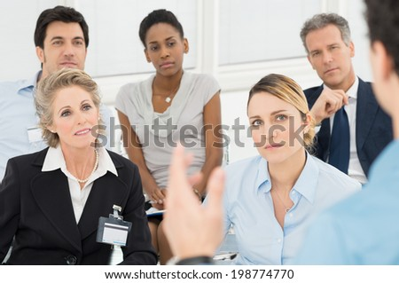 Closeup Of Businessman Giving Speech To Businesspeople At Seminar - stock photo