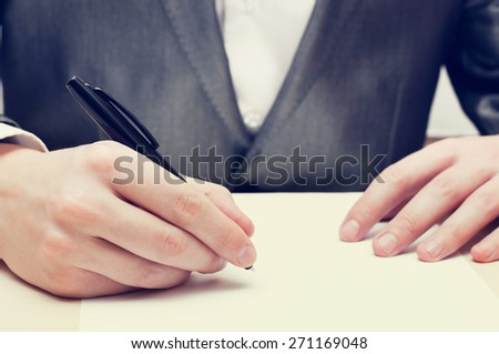 Closeup of businessman hand writing on a paper - stock photo