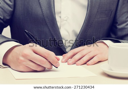Closeup of businessman hand writing on a paper at his workplace - stock photo