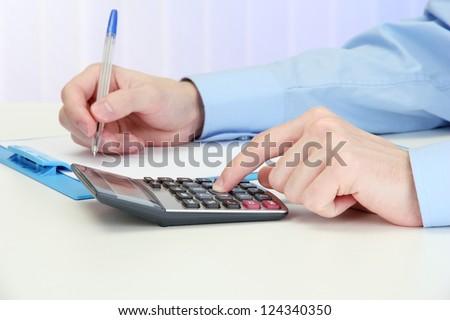 Closeup of businessman hands with calculator - stock photo
