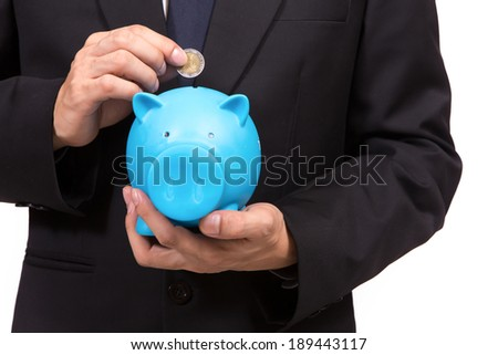 Closeup of businessman in a suit standing holding a blue piggy bank.