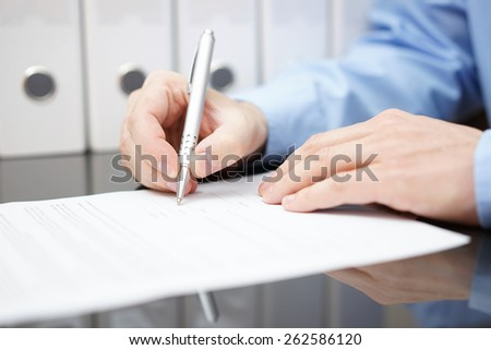 Closeup of businessman is signing contract with documentation in background - stock photo