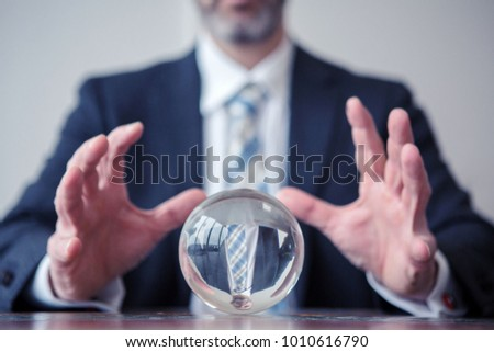 closeup of businessman looking at glass ball on table