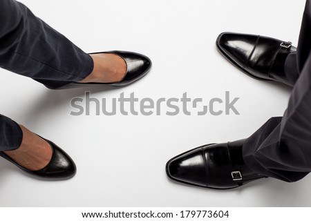 Closeup of businessman's and businesswoman's legs on the floor - stock photo