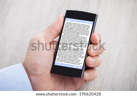 Closeup of businessman's hand displaying eBook on smartphone at desk - stock photo