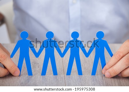 Closeup of businessman's hand holding paper people chain on desk