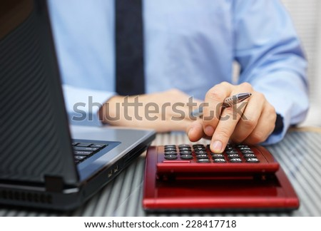 Closeup of businessman working on calculator and laptop - stock photo