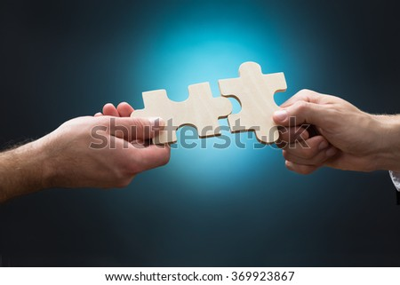 Closeup of businessmen joining jigsaw pieces against blue background