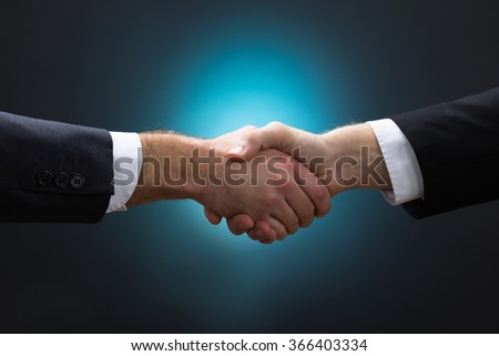 Closeup of businessmen shaking hands against blue background - stock photo