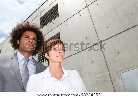 Closeup of businesspeople in front of concrete wall - stock photo