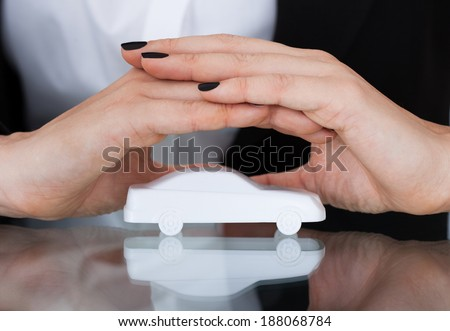 Closeup of businesswoman protecting  toy car in office - stock photo