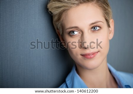 Closeup of businesswoman smiling while looking away against blue wall - stock photo