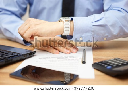 closeup of busy  Businessman watching his wrist watch  in office to be punctual - stock photo
