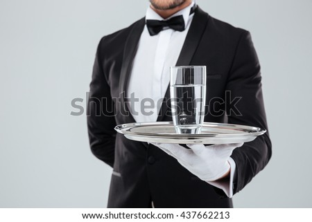 Closeup of butler in tuxedo and gloves holding silver tray with glass of water
