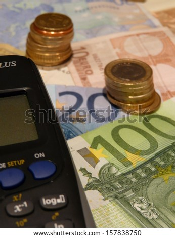 Closeup of calculator on european notes and coins background  - stock photo