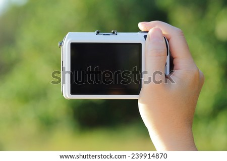 Closeup of camera taking photo picture with empty screen, nature green background - stock photo