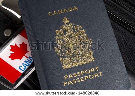Closeup of Canadian passport sitting on suitcase with maple leaf luggage tag - stock photo