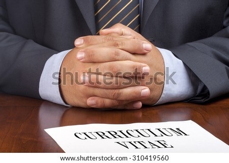 Closeup of candidate businessman with crossed hands during job interview - stock photo