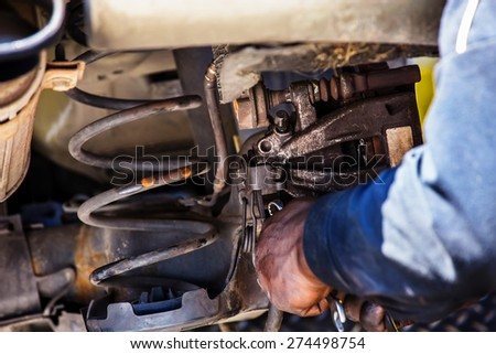 Closeup of car mechanic repairing brake pads - stock photo