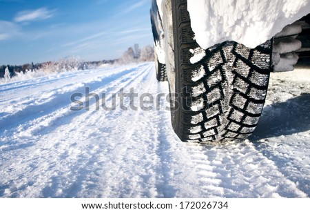 Closeup of car tires in winter morning - stock photo