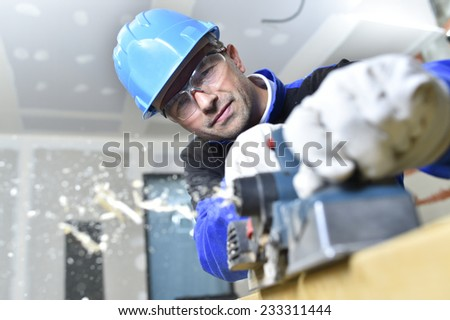 Closeup of carpenter cutting wood with electric saw - stock photo