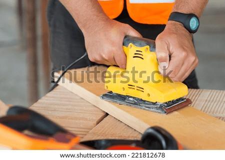 Closeup Of Carpenter Hand Sanding Plank With Electrical Sanding Machine  - stock photo