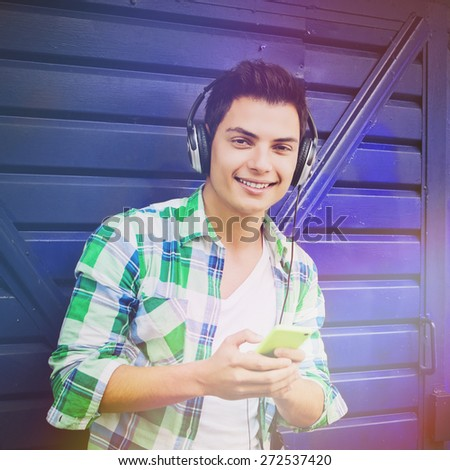 Closeup of casual millennial young mixed race man with headphones and smartphone smiling wearing green plaid shirt standing by blue garage. Natural light, retouched, filter applied, square format. - stock photo