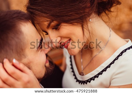 Closeup of cheerful faces of a couple leaning to each other tender