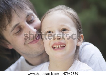 Closeup of cheerful little girl with father in park