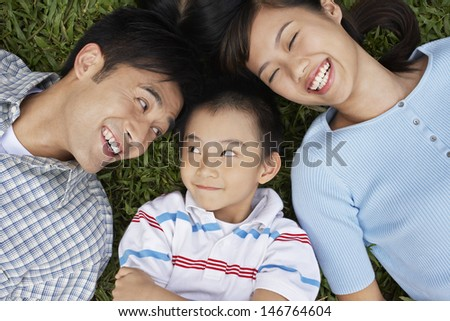 Closeup of cheerful parents with son lying on grass - stock photo