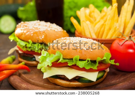Closeup of cheeseburgers and fries - stock photo
